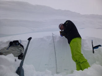 Snowpit in crown of avalanche with cornice above